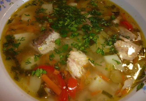 Рыбный суп с рисом, овощами и зеленью в тарелке