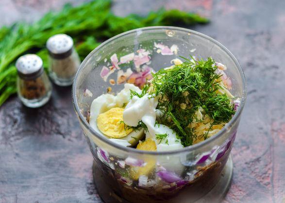 Ингредиенты для паштета из шпрот с яйцами и плавленым сыром в чаше блендера на столе