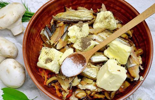 Обжаренные овощи, грибы, шпроты, сливочное масло и специи в больой миске с деревянной ложкой