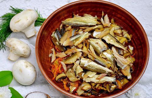 Обжаренные овощи, грибы и очищенные от костей шпротины в большой миске
