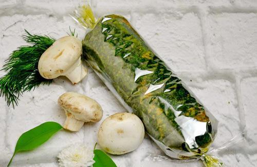 Паштет в пищевой плёнке со свежей рубленой зеленью на столе с шампиньонами