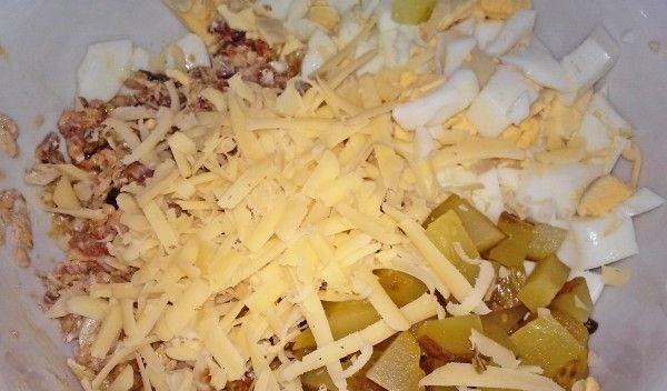 Консервированная рыба, солёные огурцы, варёные яйца и твердый сыр в миске