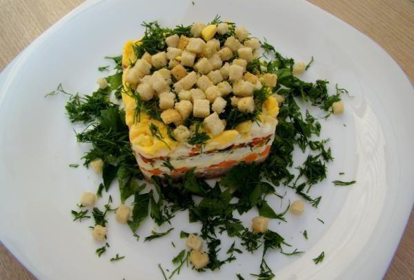 Салат из консервированной сайры с пшеничными сухариками на большой тарелке