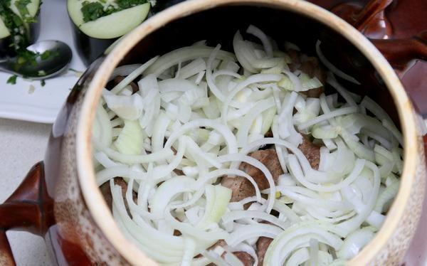 Обжаренное мясо репчатый лук в керамическом горшке