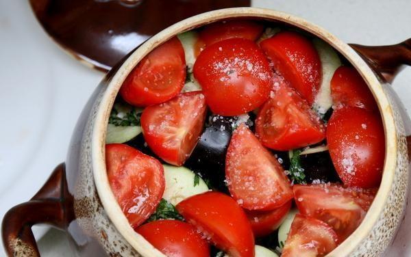Керамический горшок с кусочками овощей на столе