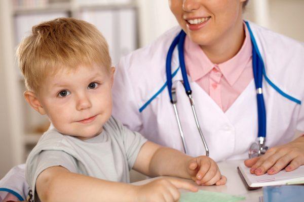 Ребёнок сидит рядом с врачом