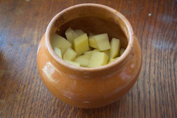 Нарезанный кубиками сырой картофель в керамическом горшочке с мясом