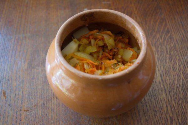 Керамический горшочек с мясом и овощами на столе