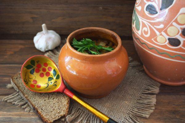 Керамический горшочек с жарким и свежей зеленью на столе с деревянной расписной ложкой