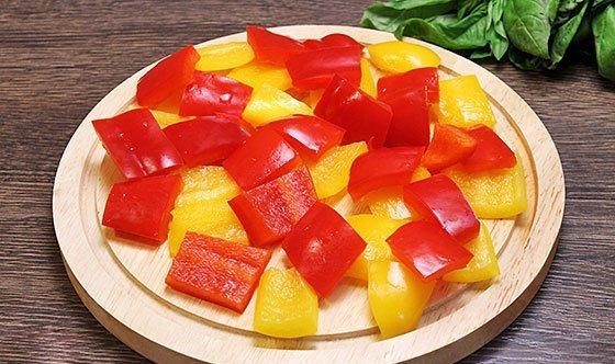 Нарезанный крупными квадратами разноцветный болгарский перец на разделочной доске