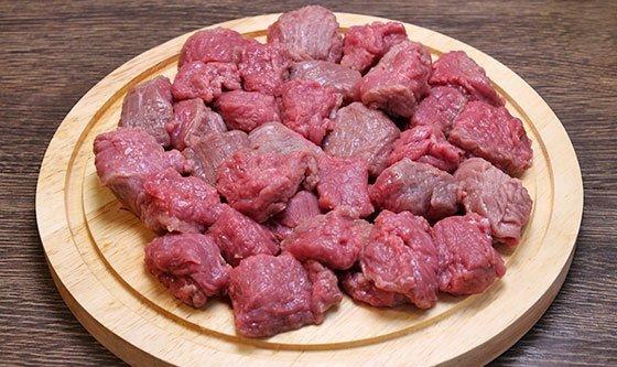 Нарезанная кусочками сырая говядина на разделочной доске