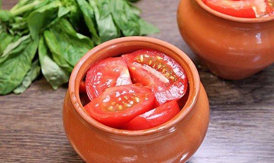 Кусочки спелых помидоров в керамическом горшочке