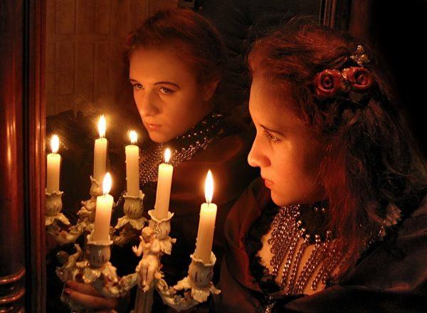Женщина стоит перед зеркалом со свечами