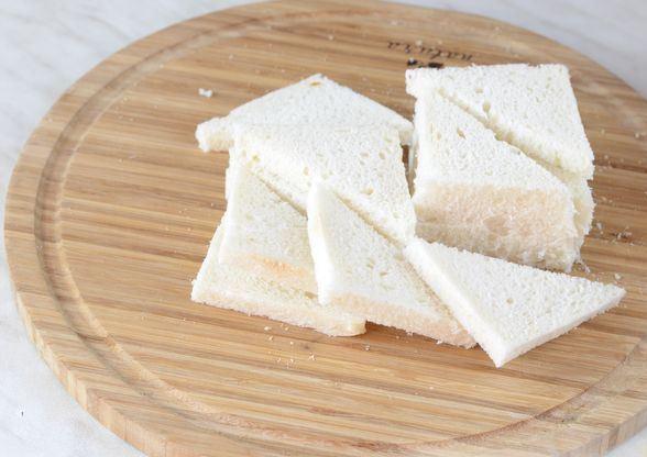 Ломтики белого хлеба без корочки на круглой разделочной доске