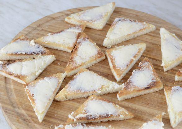 Треугольные гренки из белого хлеба с плавленым сыром на круглой разделочной доске