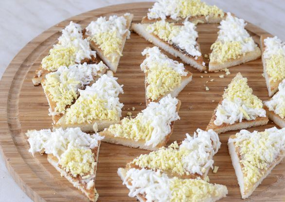 Треугольные заготовки для бутербродов с тёртым яйцом на круглой разделочной доске