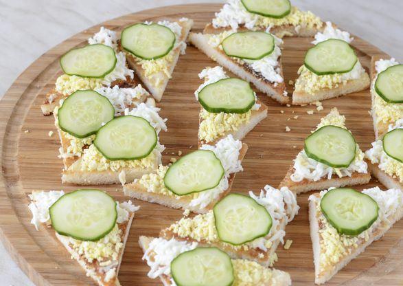 Треугольные бутерброды с отварным тёртым яйцом и свежим огурцом на разделочной доске из дерева