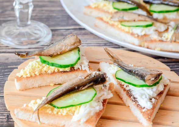 Треугольные бутерброды со шпротами, свежим огурцом и яйцами на столе