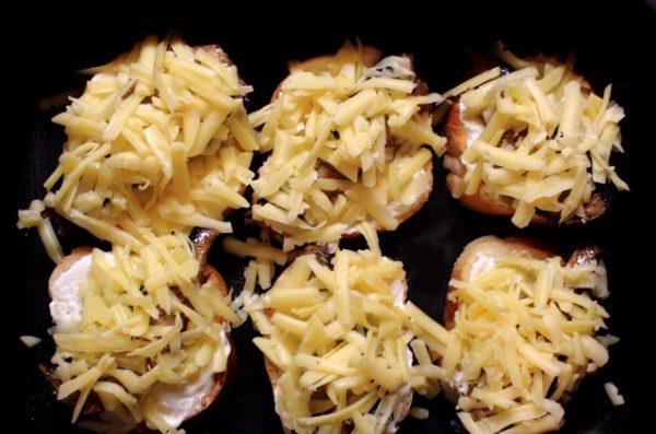 Посыпанные тёртым твёрдым сыром заготовки для бутербродов со шпротами