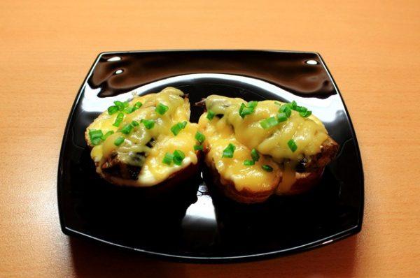 Горячие бутерброды со шпротами на прямоугольной чёрной тарелке