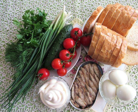 Продукты для приготовления праздничных бутербродов со шпротами и овощами на столе