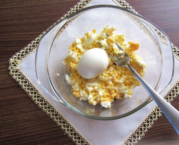 Измельчённые варёные яйца и целое варёное яйцо в стеклянной ёмкости с металлической вилкой