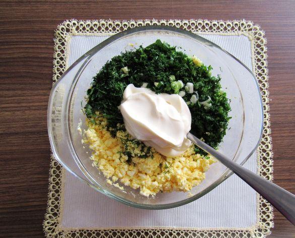 Рубленая свежая зелень, измельчённые варёные яйца и майонез в миске на столе с салфеткой