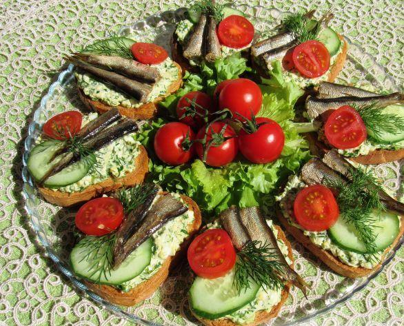 Праздничные бутерброды со шпротами на большой тарелке