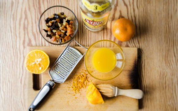 Апельсины, металлическая тёрка, апельсиновая цедра и смесь сухофруктов на столе
