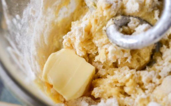 Яично-творожная масса с кусочком сливочного масла в чаше миксера
