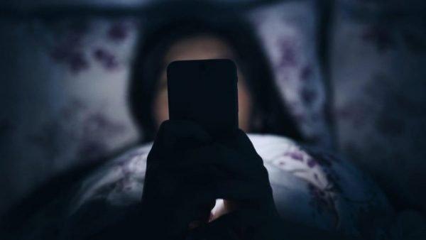 Женщина пользуется телефоном ночью