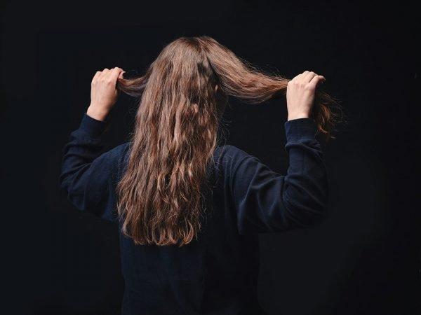 Девушка держит в руках две равные части волос на голове