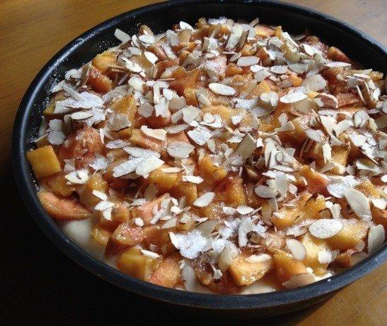 Заготовка для пирога с персиками и миндальными хлопьями в круглой форме для выпекания