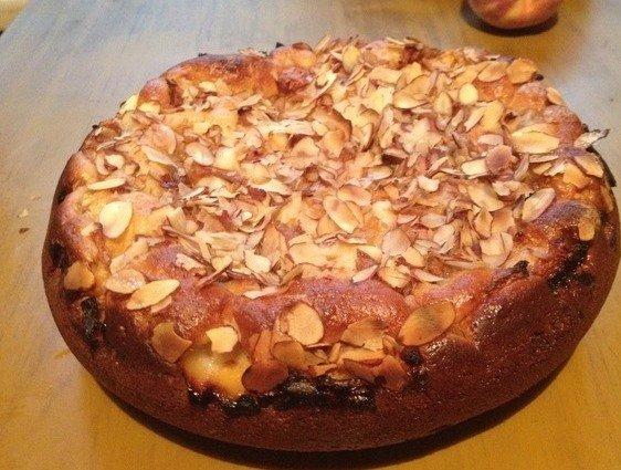 Готовый пирог с персиками и миндальными хлопьями на столе