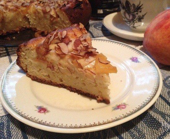 Кусочек пирога с персиками и миндальными хлопьями на тарелке
