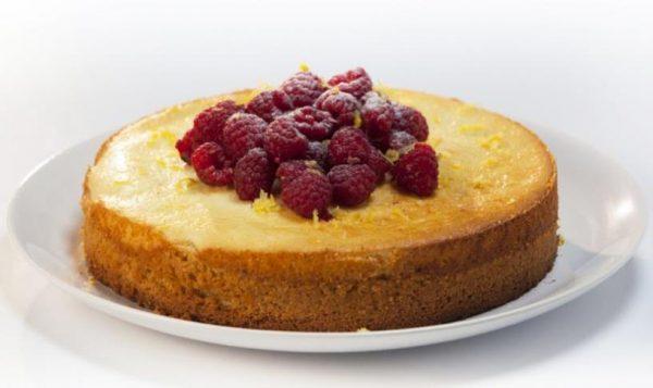 Готовый йогуртовый пирог с малиной на большой тарелке