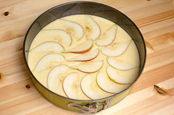 Жидкое тесто и кусочки груш в круглой форме для запекания