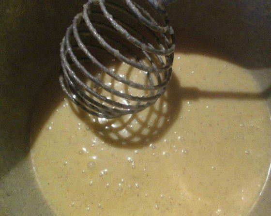 Взбитые с сахаром яичные желтки в миске с венчиком