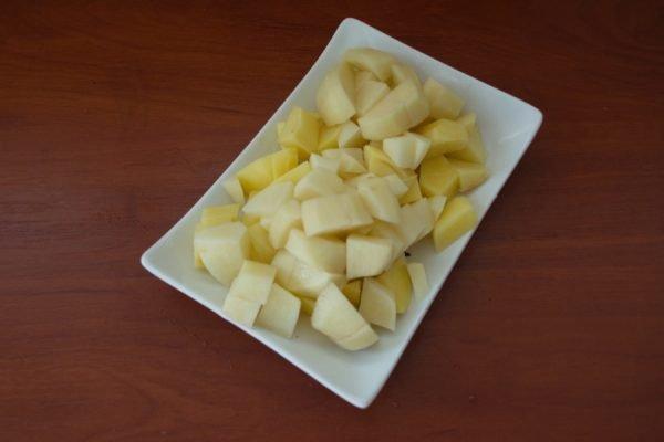 Нарезанный кубиками сырой картофель на прямоугольной белой тарелке