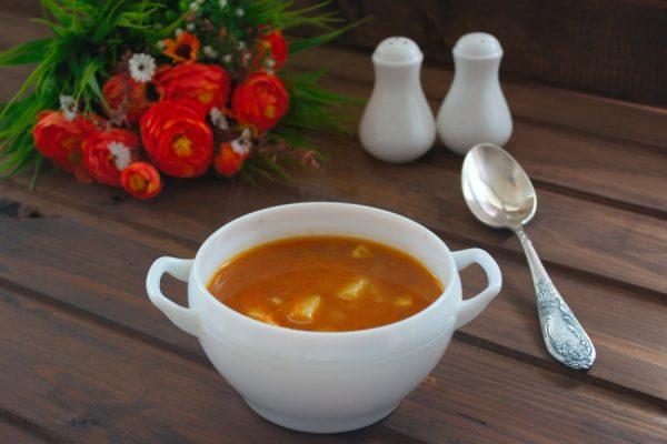 Томатный суп с картофелем, макаронами и курицей в порционной посуде на сервированном столе
