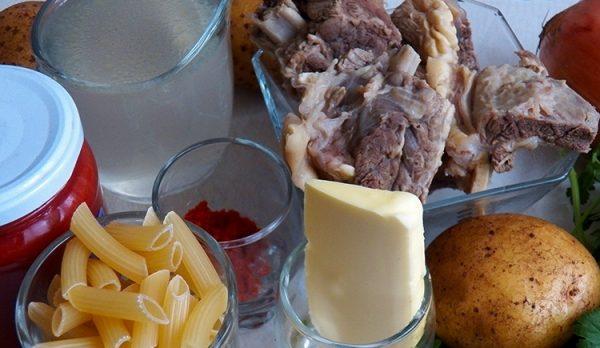 Продукты для приготовления говяжьего супа с макаронами и картофелем на столе