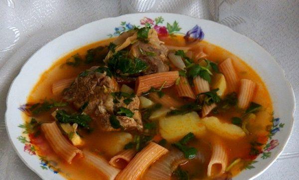 Говяжий суп с макаронами, картофелем и кинзой в порционной тарелке на столе