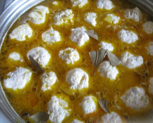 Суп с фрикадельками, овощной зажаркой и лавровым листом в большой кастрюле