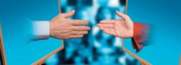 Две руки протянуты друг к другу из мониторов
