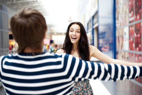 Девушка и парень раскрыли руки для приветственного объятия