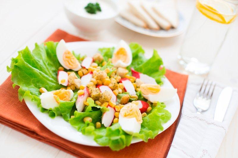 Сервированный стол с салатом из крабовых палочек