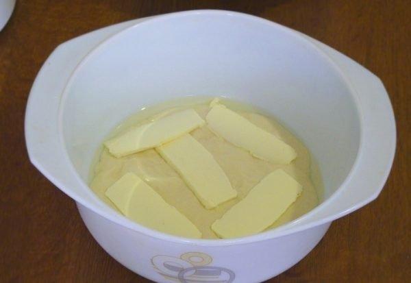 Жидкое тесто и кусочки сливочного масла в жаропрочной форме