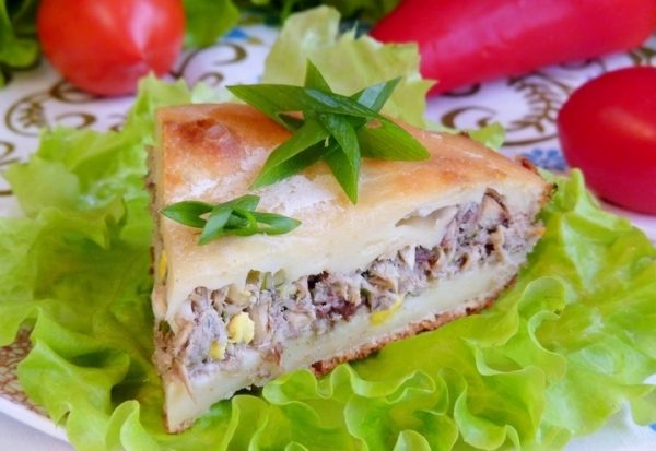 Порционный кусочек заливного пирога с рыбой и яйцом на тарелке с листьями салата