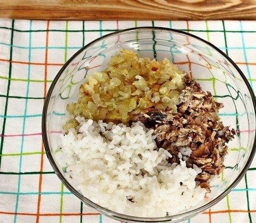 Измельчённая консервированная рыба, обжаренный репчатый лук и отварной рис в стеклянной миске