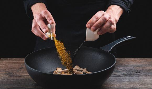Добавление соевого соуса и порошка карри к обжаренной курице